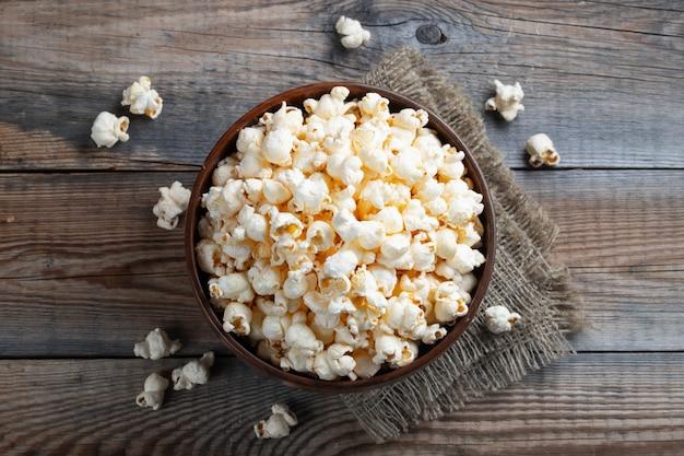 Een houten kom gezouten popcorn. Premium Foto