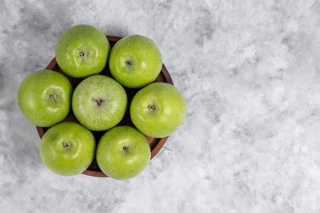 Een houten kom met verse groene zoete appels op steen Gratis Foto