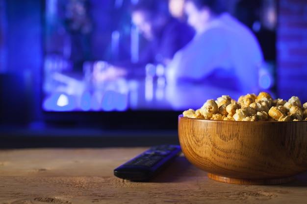 Een houten kom popcorn en afstandsbediening. Premium Foto