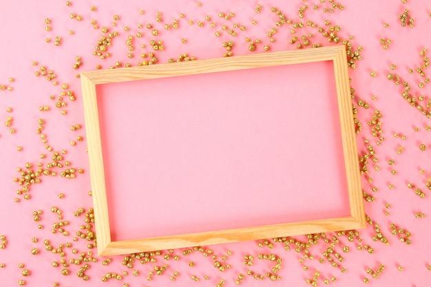 Een houten leeg frame op een pastel achtergrond omgeven door glanzende decoratieve sterren en ballen. Premium Foto