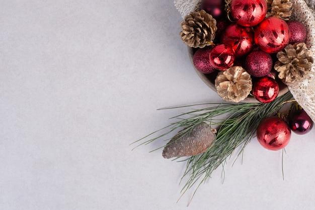 Een houten plaat van rode kerstballen en dennenappels op jute Gratis Foto