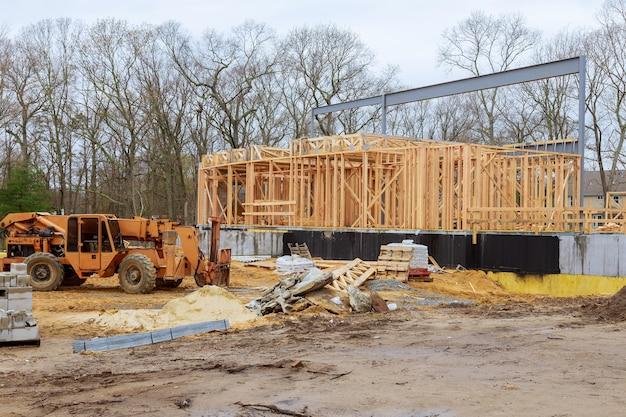 Een houten truss wordt opgetild door een vorkheftruck met giekvrachtwagen in de bouwmaterialen een stapel planken houten frame van een nieuw huis Premium Foto