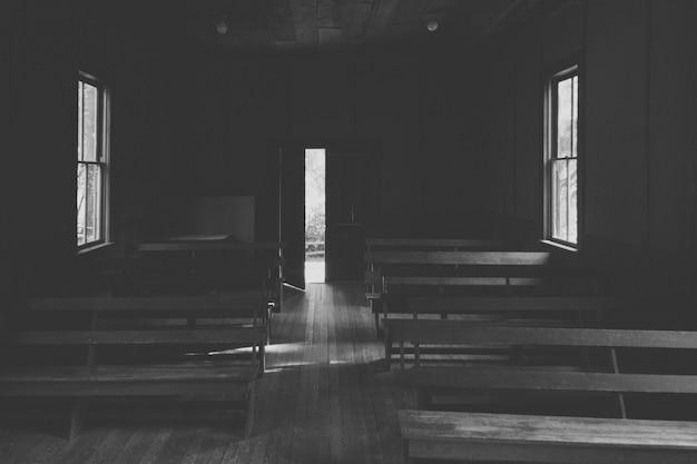 Een interieur van een kleine kerk op het platteland met houten banken en een geopende deur Gratis Foto