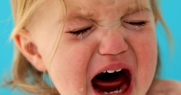 Een jaar oude baby huilt close-up Premium Foto