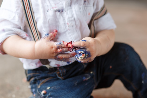 Een jaar oude jongen na het eten van een plakje verjaardag smash cake zelf vies. Gratis Foto