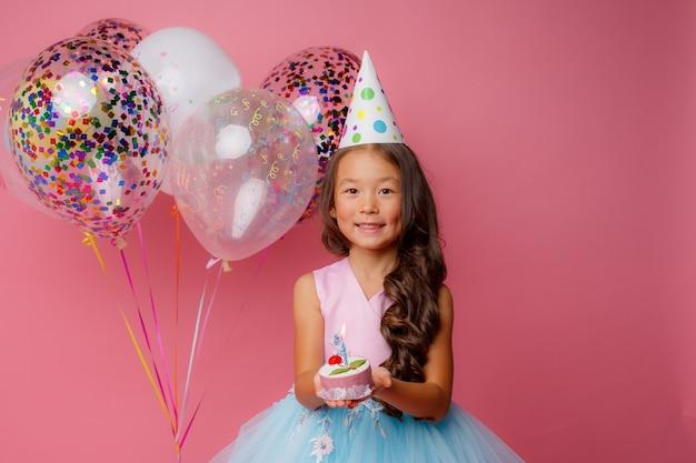 Een jong aziatisch meisje blaast een kaars uit op een roze op een verjaardagsfeestje Premium Foto
