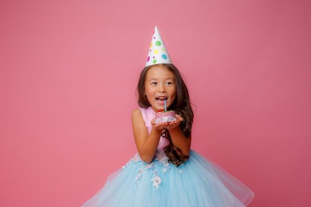 Een jong aziatisch meisje op een verjaardagsfeestje heeft een cake met een kaars op een roze Premium Foto
