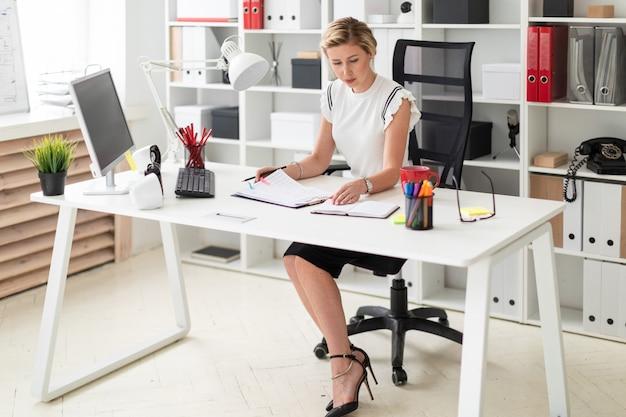 Een jong blond meisje zit achter een computerbureau op kantoor en houdt een potlood in haar hand Premium Foto
