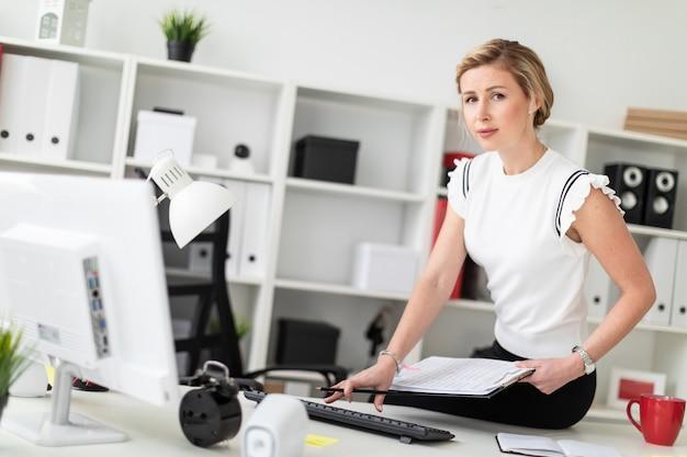 Een jong blondemeisje zit op een bureau in het bureau, houdt documenten en een potlood in haar hand en drukt op het toetsenbord. Premium Foto