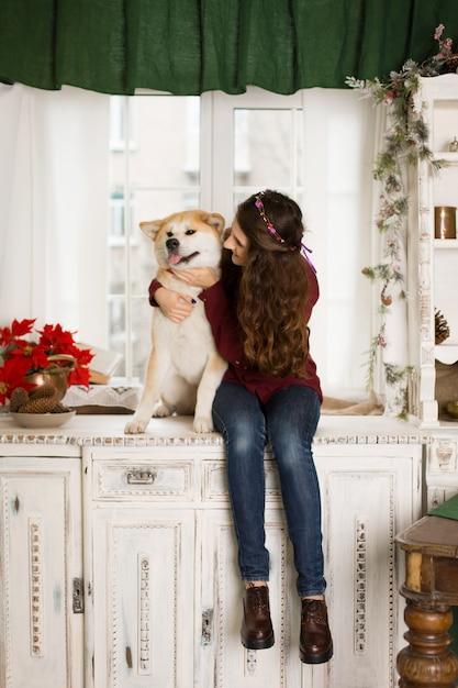 Een jong droevig meisje met een gehoorzame hond zit op een dressoir bij het raam Premium Foto