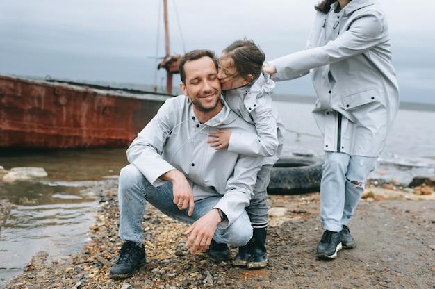 Een jong gezin heeft een plezier in de buurt van de zee op de achtergrond van een boot Premium Foto
