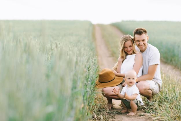 Een jong gezin heeft plezier met hun kleine baby in het veld Premium Foto