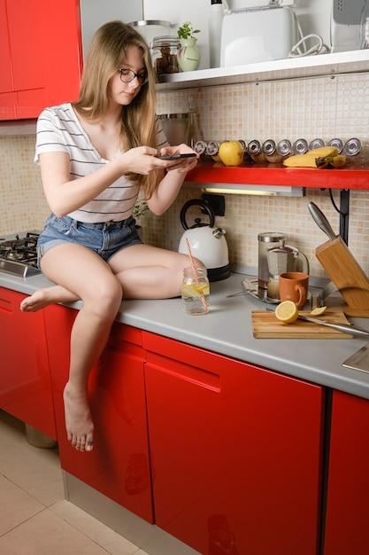 Een jong meisje blogger maakt een foto van haar drankje om het op de keukentafel te laten zien op sociale media Premium Foto