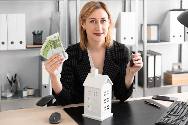 Een jong meisje dat geld en sleutels houdt. voor haar op tafel staat de indeling van het huis. Premium Foto