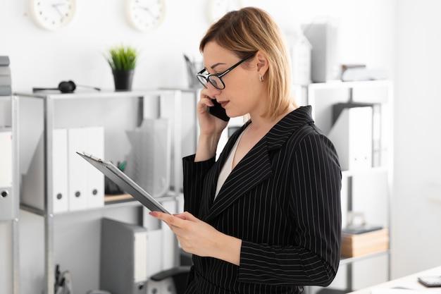 Een jong meisje dat zich in het kantoor bevindt en de telefoon spreekt. Premium Foto