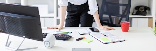 Een jong meisje dat zich in het kantoor bij de computerlijst bevindt. Premium Foto
