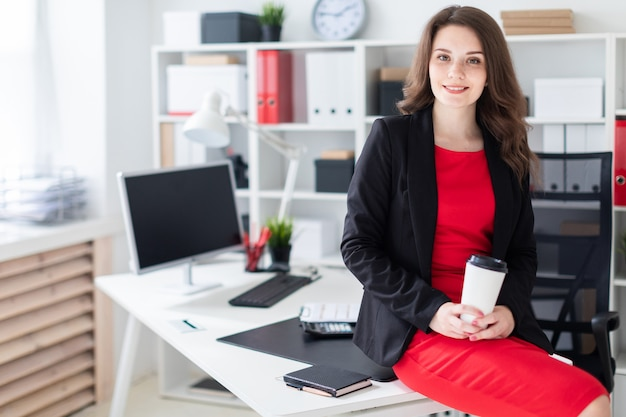 Een jong meisje ging op een tafel in het kantoor zitten en hield een glas koffie vast. Premium Foto