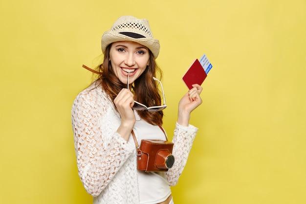 Een jong meisje heeft een kaartje met een paspoort en een camera op een gele achtergrond Premium Foto
