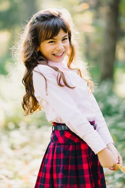Een jong meisje in de herfst van het park glimlacht Premium Foto