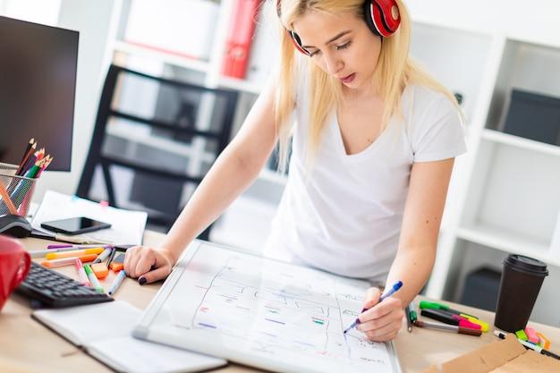 Een jong meisje in de koptelefoon staat bij de tafel en houdt een marker in haar hand. Premium Foto