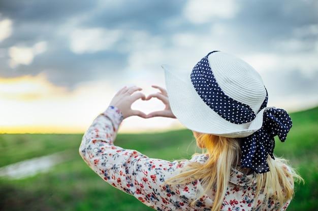 Een jong meisje in een hoed die hartsymbool met haar handen maakt bij zonsondergang. Premium Foto