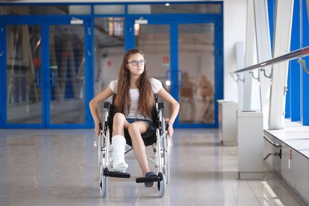 Een jong meisje in een rolstoel staat in de gang van het ziekenhuis. Premium Foto