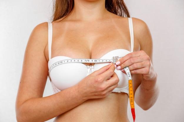 Een jong meisje in witte lingerie meet haar borsten met een meter. Premium Foto