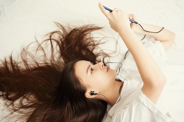 Een jong meisje ligt thuis op een bed met haar haar uitgespreid Premium Foto