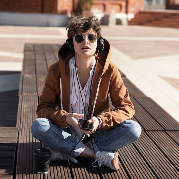 Een jong meisje met een stijlvol kort kapsel zit op een bankje en luistert naar muziek op de koptelefoon. Premium Foto