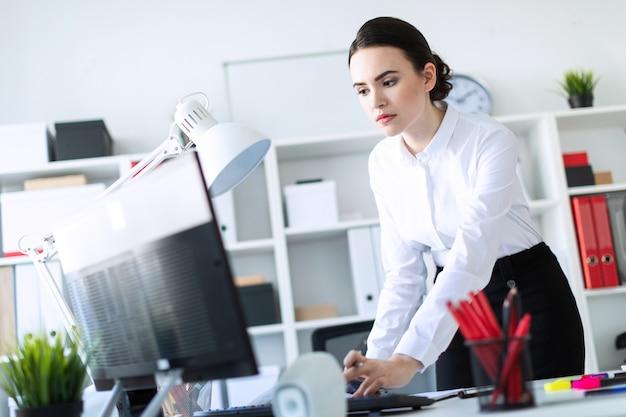 Een jong meisje op kantoor staat bij de tafel, houdt een potlood in haar hand en typt de tekst op de computer. Premium Foto