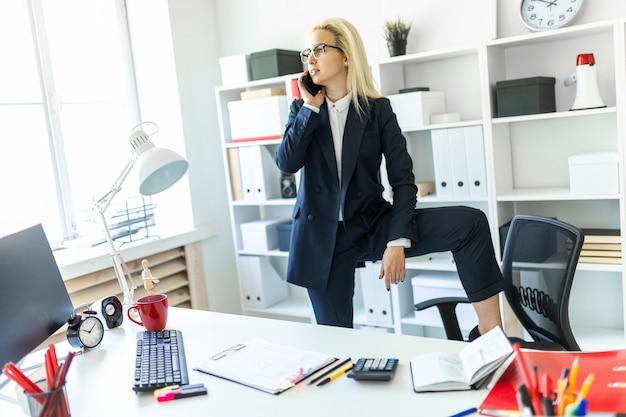 Een jong meisje staat bij een tafel op kantoor, zet haar voet op een stoel en praat aan de telefoon. Premium Foto