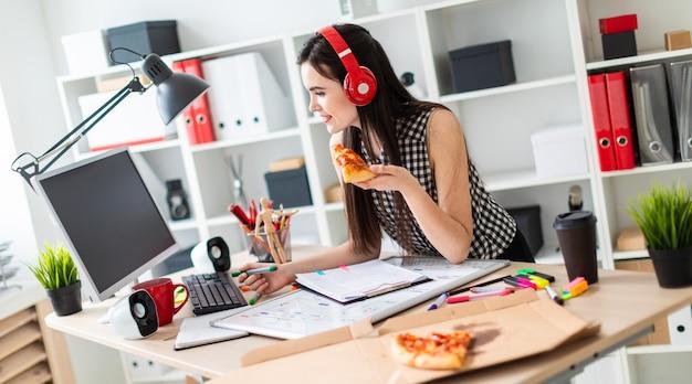 Een jong meisje staat in de buurt van een tafel, met een groene marker en een stuk pizza in haar hand. Premium Foto