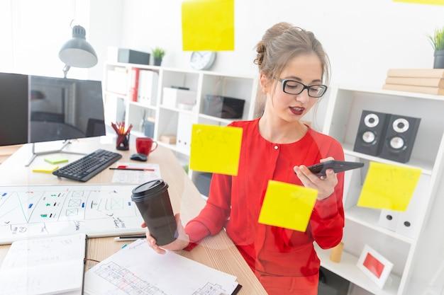Een jong meisje staat in de buurt van een transparant bord met stickers en houdt een glas met koffie en telefoon vast. Premium Foto