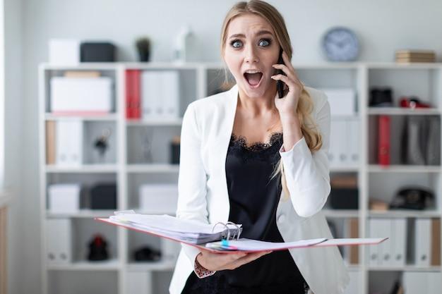 Een jong meisje staat op kantoor naast de planken, aan de telefoon en houdt een map met documenten vast. Premium Foto