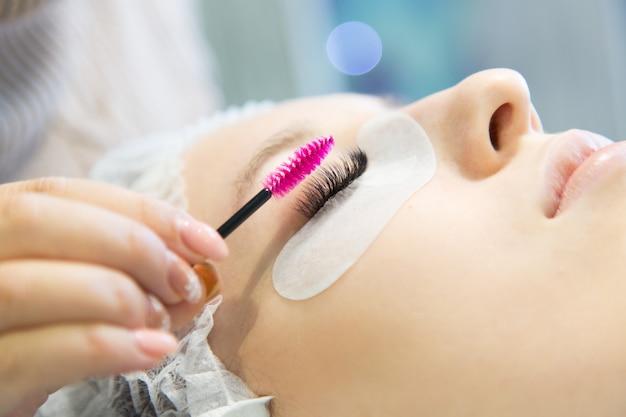 Een jong meisje verhoogt wimpers in een schoonheidssalon. Premium Foto