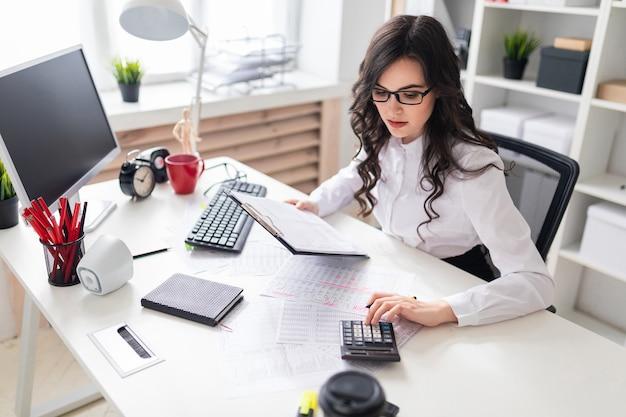 Een jong meisje zit aan het bureau en zegen op de rekenmachine. Premium Foto