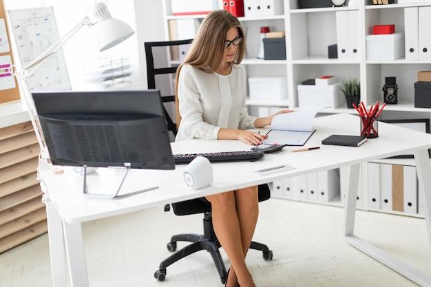 Een jong meisje zit achter het computerbureau op kantoor, houdt een potlood in haar hand en maakt aantekeningen in het document. Premium Foto