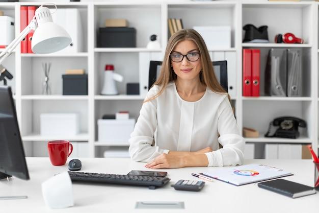 Een jong meisje zit achter het computerbureau op kantoor. Premium Foto