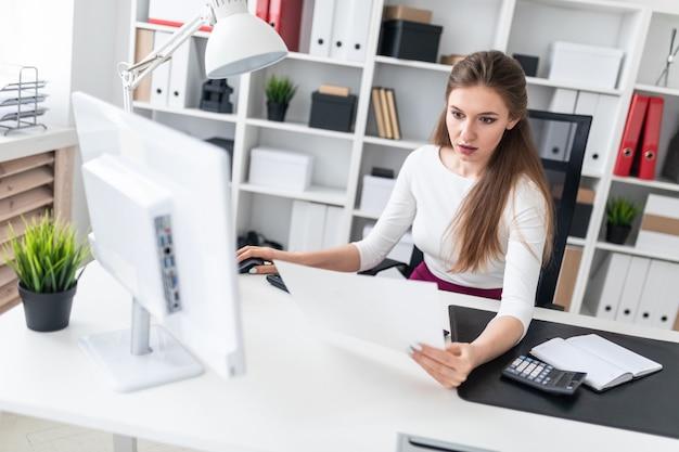 Een jong meisje zit op een computer bureau en werkt met documenten. Premium Foto