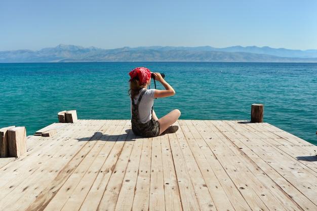 Een jong meisje zit op een houten pier en kijkt door een verrekijker. Premium Foto
