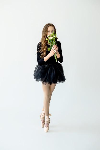 Een jong mooi ballerinameisje staat op pointe-schoenen in een zwart zwempak en een rok met bloemen in haar handen op een lichte achtergrond. Premium Foto