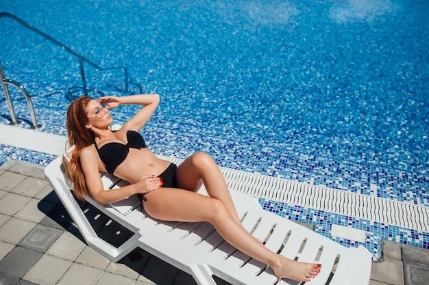 Een jong mooi bruinharig meisje met grote hoeden in een zwart zwempak en zonnebril Premium Foto