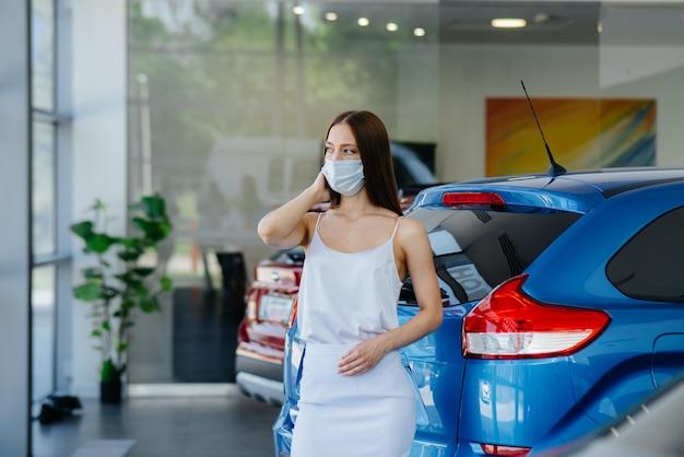 Een jong mooi meisje inspecteert tijdens de pandemie een nieuwe auto bij een autodealer in een masker. de aan- en verkoop van auto's, in de periode van pandemie. Premium Foto