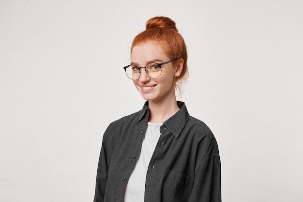 Een jong roodharig meisje staat in een halve draai en kijkt door een bril naar de camera. Gratis Foto