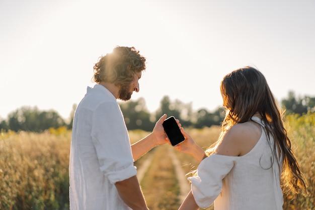 Een jong stel in de natuur kijkt naar de telefoon. Premium Foto