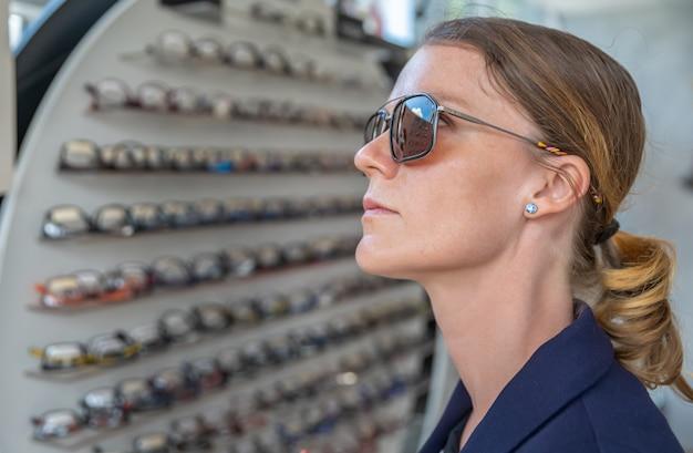Een jonge aantrekkelijke vrouw in een optiekwinkel probeert een nieuwe bril Premium Foto