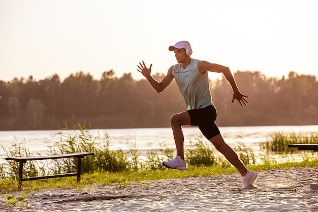 Een jonge atletische man traint het luisteren naar de muziek aan de rivier buiten Gratis Foto