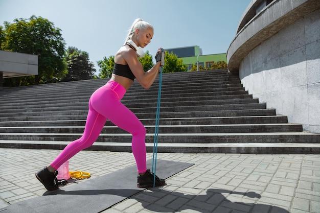 Een jonge atletische vrouw die aan het trainen is in de straat van de stad Gratis Foto