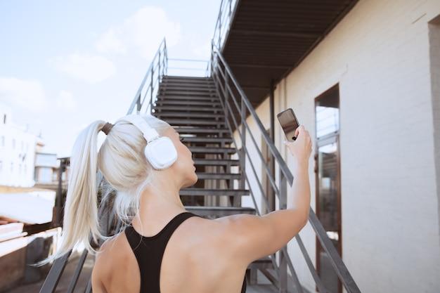 Een jonge atletische vrouw in overhemd en witte hoofdtelefoons die aan de muziek op een trap in openlucht uitwerken Gratis Foto