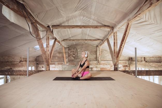 Een jonge atletische vrouw in overhemd en witte hoofdtelefoons die aan de muziek op een verlaten bouwplaats uitwerken Gratis Foto